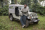 Owner of a coffee plantation in front of his Jeep, potrait. Coorg or Kadagu is the largest coffee growing region of India, in the state of Karnataka, the inhabitants - the Kodavas have been cultivating crops such as coffee, black pepper and cardamon for many generations.