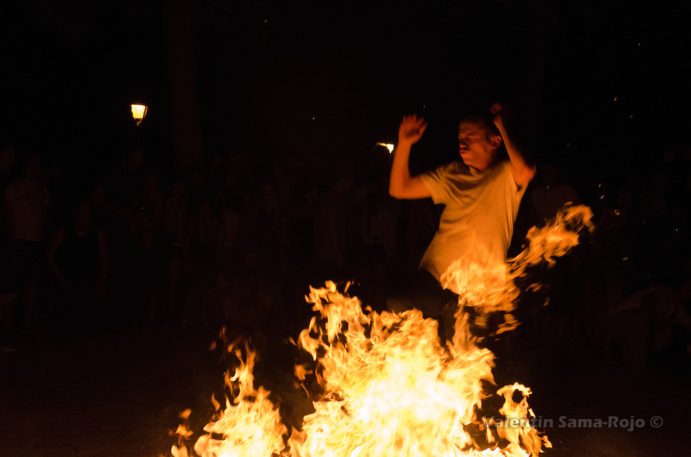 Close up of a man jumping through the fire of a bonfire during Saint John's Eve in Madrid.