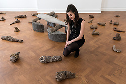 """© Licensed to London News Pictures. 17/04/2018. LONDON, UK. A staff member views 38 clay sculptures called """"Urtiere (Primordial Animals)"""", 1958/1982, with """"Hirsch (Stag)"""", 1958/1982, a teak wood and wooden ironing board that belonged to the artist's mother behind her, at the preview of """"Joseph Beuys: Utopia at the Stag Monuments"""", at the Galerie Thaddaeus Ropac in Dover Street.  The retrospective is the most important UK exhibition of Beuys' work in over a decade, presenting major sculptures and rarely seen works from 1947 to 1985, and runs from 18 April to 16 June.  Photo credit: Stephen Chung/LNP"""