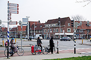 In Utrecht wachten vrouwen met hun fiets voor het verkeerslicht bij een grote kruising.<br /> <br /> In Utrecht women are waiting with their bicycles for a traffic light near a big crossing.