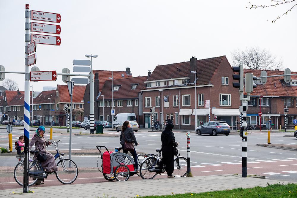 In Utrecht wachten vrouwen met hun fiets voor het verkeerslicht bij een grote kruising.<br /> <br /> In Utrecht women are waiting with their bicycles for a traffic light near a big crossing.