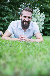 Portrait of a happy young man lying in garden, Bavaria, Germany
