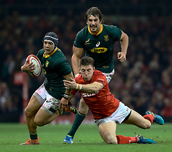 Cheslin Kolbe of South Africa evades the tackle of Josh Adams of Wales<br /> <br /> Photographer Simon King/Replay Images<br /> <br /> Under Armour Series - Wales v South Africa - Saturday 24th November 2018 - Principality Stadium - Cardiff<br /> <br /> World Copyright © Replay Images . All rights reserved. info@replayimages.co.uk - http://replayimages.co.uk