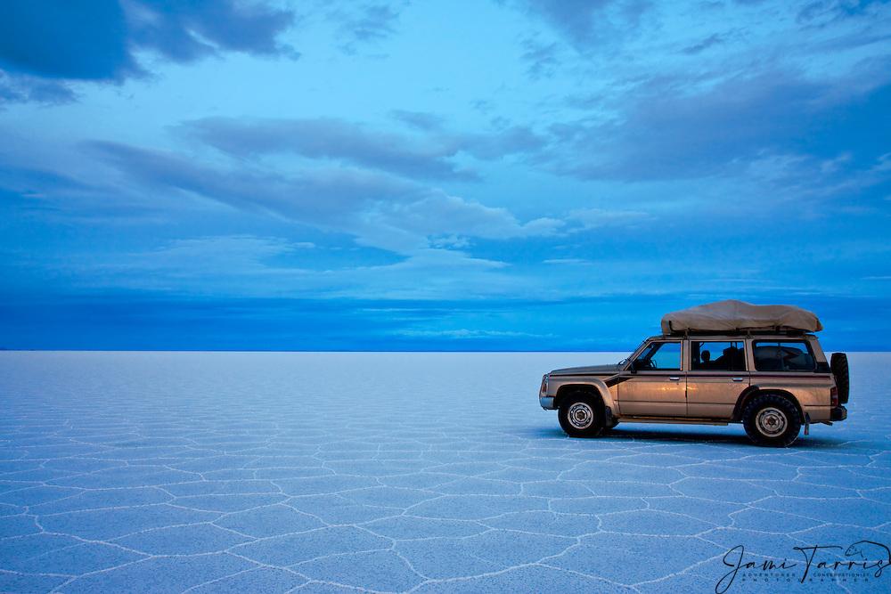 Tourist vehicle sitting on salt hexagon patterns awash in twilight blue on the Salar de Uyuni,  Bolivia,South America