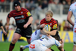 Saracens Flanker (#6) Jackson Wray is tackled by Exeter Chiefs Hooker (#2) Neil Clark during the second half of the match - Photo mandatory by-line: Rogan Thomson/JMP - Tel: Mobile: 07966 386802 16/02/2013 - SPORT - RUGBY - Allianz Park - Barnet. Saracens v Exeter Chiefs - Aviva Premiership. This is the first Premiership match at Saracens new home ground, Allianz Park, and the first time Premiership Rugby has been played on an artificial turf pitch.