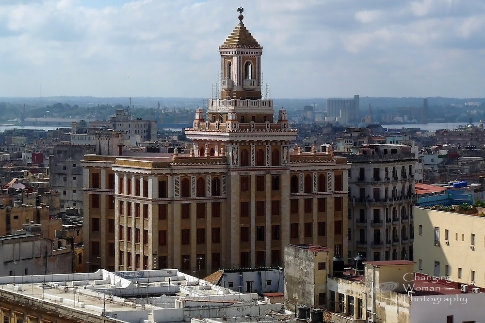 """Built in 1930, the Bacardi building's art deco maginificence still rises above historic Old Havana, an architectural treasure. The famous """"black bat on red globe"""" that is the Bacardi logo adorns the building's cupola.  This view of the Bacardi building from an upper floor of the Hotel Sevilla looks east over the city, the bay, and East Havana beyond."""