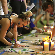 A woman is seen signing a makeshift memorial during a vigil at the Dr. Phillips Center for the Performing Arts for the victims of a mass shooting at the Pulse nightclub Monday, June 13, 2016, in Orlando, Florida.  A gunman killed dozens of people in a massacre at the crowded gay nightclub in Orlando on Sunday, making it the deadliest mass shooting in modern U.S. history. (Alex Menendez via AP)