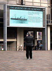 A man takes a photograph of the giant screen as members of the South African Diaspora Choristers are joined by pupils of St Johns Cathedral Primary School and Chicester Community Choir for a memorial at Portsmouth Guildhall in Hampshire, to those who lost their lives on the troop ship SS Mendi.