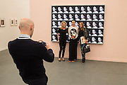 A man takes a photo of a group of women, one wearing a top with an image from the photo collage  behind them. Photos by Linder Sterling, in the gallery of Stuart Shave / Modern Art.