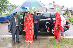 Bride in traditional Asian dress and her family arriving for her wedding,