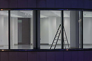 Stepladders seen in a still vacant office space in the City of London, UK. The ladders stand, left alone for the night. The corporate floors are new, currently unoccupied by the tenant or owner and with fixtures, fittings and furnishings still to be fitted by the property's management. Work has yet to be completed before the hundreds or thousands of employees can move in to this building in the heart of the UK capital's financial district, founded by the Romans in AD43.