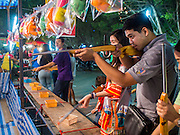 "07 MARCH 2015 - NAKHON CHAI SI, NAKHON PATHOM, THAILAND: A target shooting arcade game at the Wat Bang Phra tattoo festival. Wat Bang Phra is the best known ""Sak Yant"" tattoo temple in Thailand. It's located in Nakhon Pathom province, about 40 miles from Bangkok. The tattoos are given with hollow stainless steel needles and are thought to possess magical powers of protection. The tattoos, which are given by Buddhist monks, are popular with soldiers, policeman and gangsters, people who generally live in harm's way. The tattoo must be activated to remain powerful and the annual Wai Khru Ceremony (tattoo festival) at the temple draws thousands of devotees who come to the temple to activate or renew the tattoos. People go into trance like states and then assume the personality of their tattoo, so people with tiger tattoos assume the personality of a tiger, people with monkey tattoos take on the personality of a monkey and so on. In recent years the tattoo festival has become popular with tourists who make the trip to Nakorn Pathom province to see a side of ""exotic"" Thailand.   PHOTO BY JACK KURTZ"