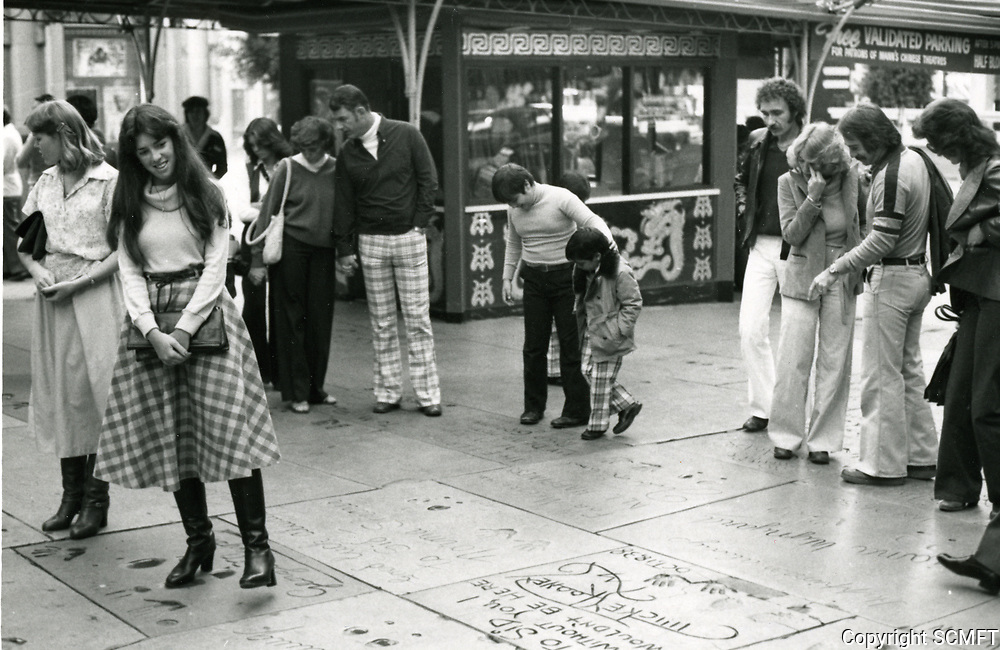 1985 Tourists looking at the hand and footprints in the Chinese Theatre forecourt