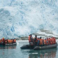 Adventure travelers in zodiac rafts float below a glacier icefall in the Cordillera Darwin that flows into Seno Chico, a small fjord in Alberto De Agostini National Park, Tierra del Fuego, Chile.