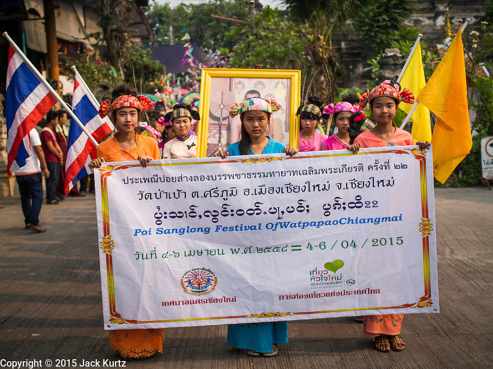 """05 APRIL 2015 - CHIANG MAI, CHIANG MAI, THAILAND: Tai Yai women lead a parade of Buddhist novices during the second day of the three day long Poi Song Long Festival in Chiang Mai. The Poi Sang Long Festival (also called Poy Sang Long) is an ordination ceremony for Tai (also and commonly called Shan, though they prefer Tai) boys in the Shan State of Myanmar (Burma) and in Shan communities in western Thailand. Most Tai boys go into the monastery as novice monks at some point between the ages of seven and fourteen. This year seven boys were ordained at the Poi Sang Long ceremony at Wat Pa Pao in Chiang Mai. Poy Song Long is Tai (Shan) for """"Festival of the Jewel (or Crystal) Sons.    PHOTO BY JACK KURTZ"""