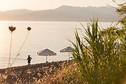 Man fishing on sea beach at sunset, Neo Chorio, Cyprus