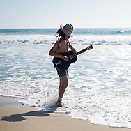 A musician plays his guitar at the beach in Puerto Escondido, Oaxaca State, Mexico.<br /> <br /> (November 2014)
