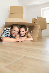 Couple smiling inside cardboard box new home