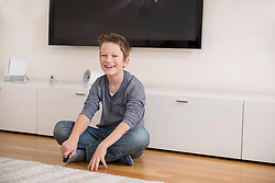 Smiling boy sitting on floor in living room