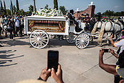 George Floyd's casket, carried by horse and carriage, turns into the cemetery during George Floyd's funeral procession in Houston, TX Tuesday June 9.