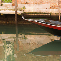 Typical Venetian boat adorned with water reflection