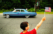 Seven-year old Anthony Orechio displays his patriotism as a classic car cruises by during the Ocean Township Memorial Day parade held along Monmouth Road in Oakhurst, New Jersey on May 28, 2007.