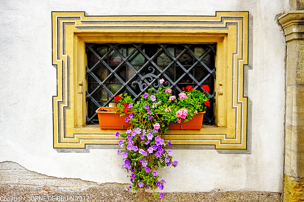 A steel barred window decorated with flowers in the old town of Regensburg, Germany