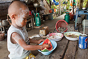 Apr. 3, 2010 - KHUN SAMUTCHINE, THAILAND: A boy eats a watermelon in his home in Khun Samutchine. Rising sea levels brought about by global climate change threaten the future of Khun Samutchine, a tiny fishing village about 90 minutes from Bangkok on the Gulf of Siam. The coastline advances inland here by about 20 metres (65 feet) per year causing families to move and threatening the viability of the village. The only structure in the village that hasn't moved, their Buddhist temple, is completely surrounded by water and more than 2 kilometers from the village. The temple and the village have asked the Thai government and several NGOs for help, but the only help so far is a narrow concrete causeway the government is building that will allow people to walk into the temple from a boat landing two miles away. The walk to the village from a closer boat landing is shorter, but over an unimproved mud flat that is nearly impassible in the rainy season.  PHOTO BY JACK KURTZ