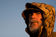 Hunter John Davidson duck hunting at dawn on a hilltop south-east of Minot. The duck hunters travel in the dark to the place they suspect will be the morning feeding roost for ducks. As the sun comes up they have prepared decoys in the field and hide behind some undergrowth in their camouflage clothing. As the sun rises soem ducks take to the air for their morning feed. As they draw near the hunters make female and feeding duck calls to attract the flying birds towards the decoys and to within shooting range. The moment they are close enough the hunters quickly take aim anf fire their shotguns; some of the ducks fall to the ground. A great deal of work and effort goes into this type of shooting, with the result being a few fine Mallards for the pot.