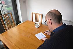 Man completing his postal vote - general election December 2019 UK. MR