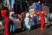 A group of children's costume characters, including Elmo from Sesame Street and Elsa from Frozen, stand waiting to interact with tourists in Times Square, Midtown Manhattan, New York City, New York, United States.  In 2016, Mayor de Blasio signed a law to declare pedestrian plazas, like Times Square to be no-soliciting zones due to the ongoing issues of costume characters harassing tourists for money.