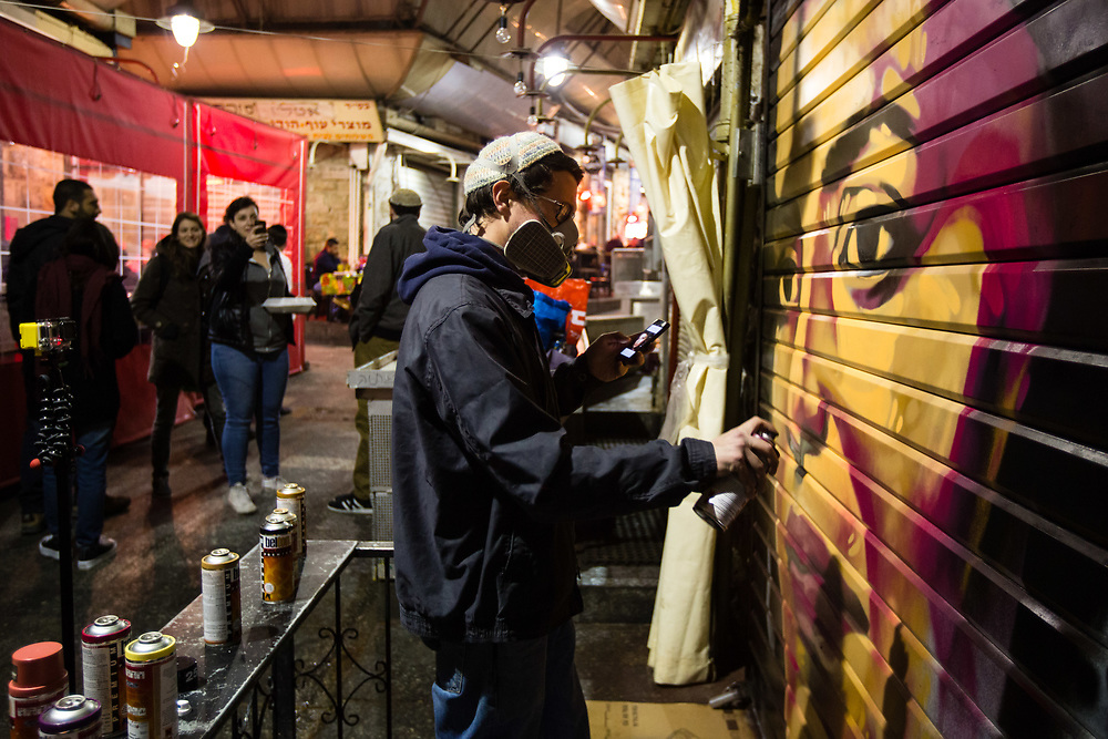 People watch artist Solomon Souza (R) as he spray-paints a portrait depicting Israeli-Arab news anchor Lucy Aharish over a closed shutter at the Mahane Yehuda Market, often called 'The Shuk' in Jerusalem, Israel, on February 24, 2016.