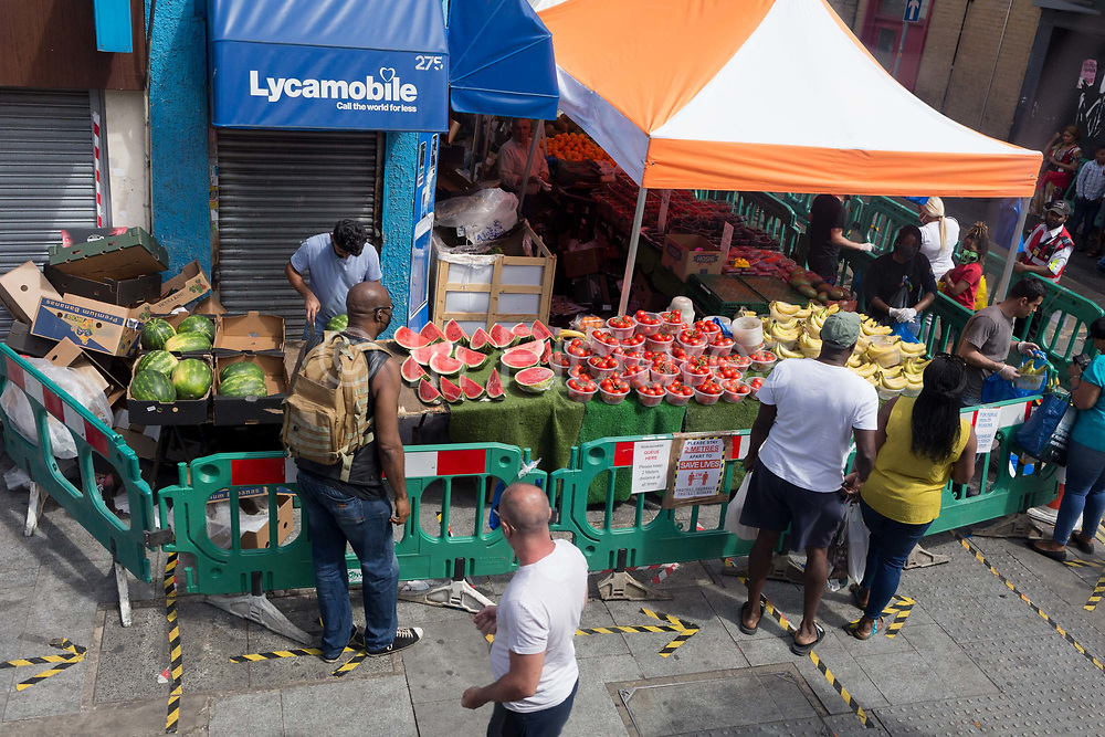 During the UKs Coronavirus pandemic lockdown and in the 24hrs when a further 255 deaths occurred, bringing the official covid deaths to 37,048, <br /> shoppers at a fruit and veg stall practice social distancing at East Street Market on the Walworth Road, on 26th May 2020, in London, England.