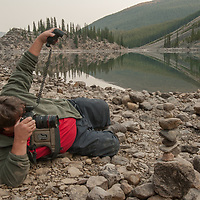 A photographer uses a flash to help light a scence beside Moraine Lake in Banff National Park, Alberta, Canada.