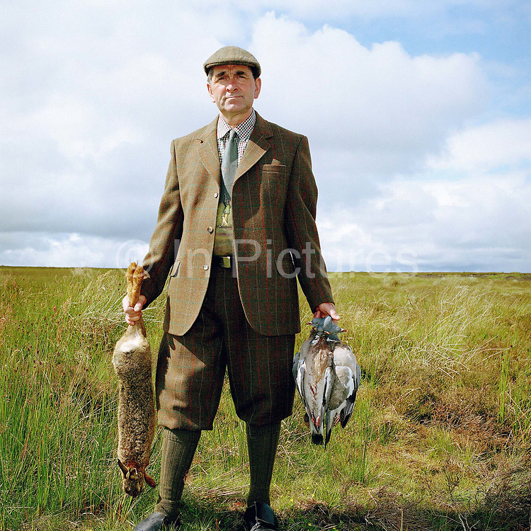 Portrait of gamekeeper Ronnie Grigor holding a hare and wood pigeions at Fala estate, Midlothian, Scotland. Fala estate supplies game such as roe deer (venison), hares, rabbits and wood pigeons to local restaurants.