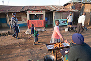 A girl buys a fried pastry from a vendor in the Kibera slum in Nairobi, Kenya. Kibera is Africa's biggest slum with nearly one million inhabitants.