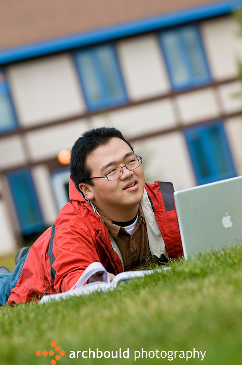 Student studies outdoors on college campus with laptop.