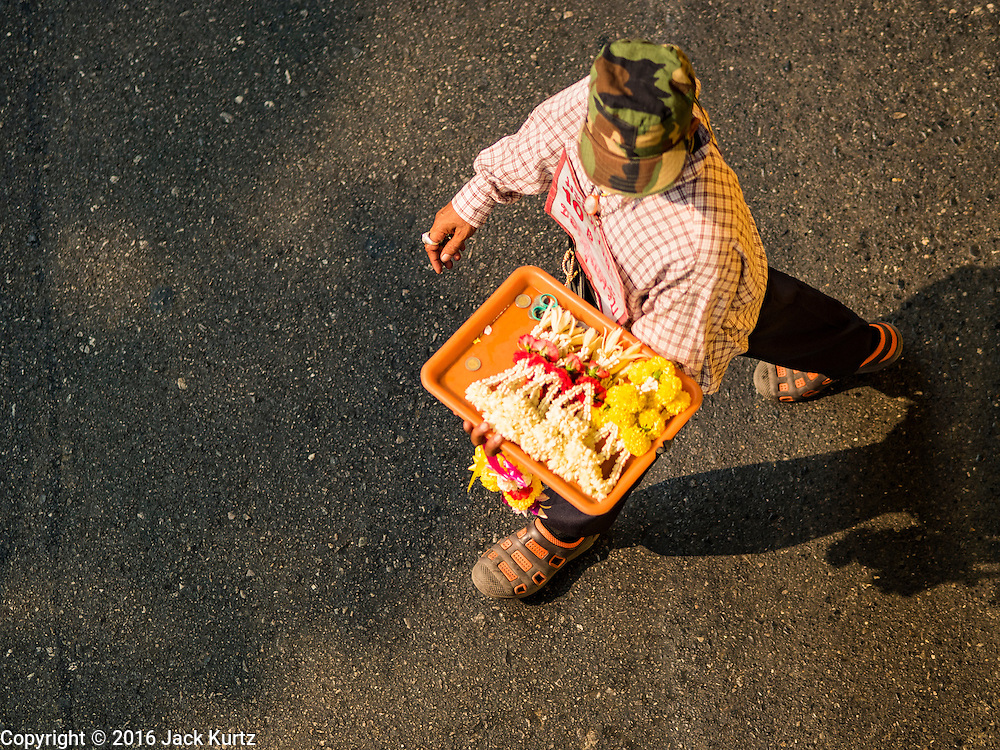 23 MARCH 2016 - BANGKOK, THAILAND: A flower garland vendor walks between vehicles in traffic in Bangkok, Thailand. Flower garlands are frequently used as talismans by Thai taxi drivers.      PHOTO BY JACK KURTZ