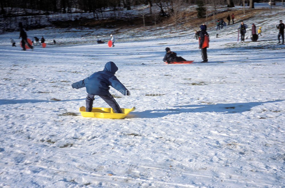 A young boy snow boarding on his sleigh