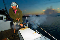 Captain Owen Dorr firing his cannon at sunset, Schooner Nathaniel Bowditch in Pulpit harbor, Penobscot Bay, Maine USA