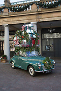 A green Morris Minor 1000 with Christmas presents loaded to the roof at Covent Garden Market on the 11th December 2018 in London in the United Kingdom.