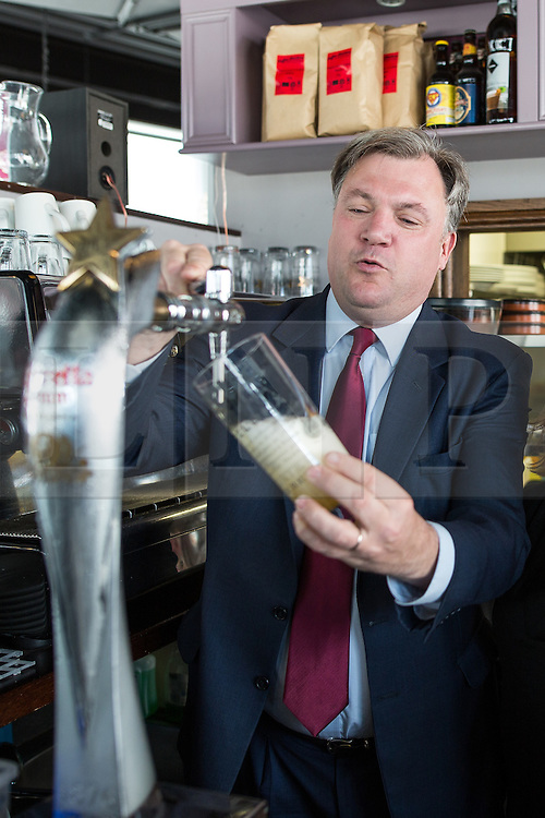 © Licensed to London News Pictures . 11/04/2015 . Bury , UK . Labour Shadow Chancellor ED BALLS pours a pint . Ed Balls and James Frith , Labour candidate for Bury North , at a campaign stop at Barista coffee shop at The Rock , Bury in Greater Manchester , UK . The pair met parents and discussed family finances . Photo credit : Joel Goodman/LNP