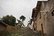 A young man walks down a long flight of stairs in an empty street in the outskirts of San Cristobal de las Casas, Chiapas state, Mexico.