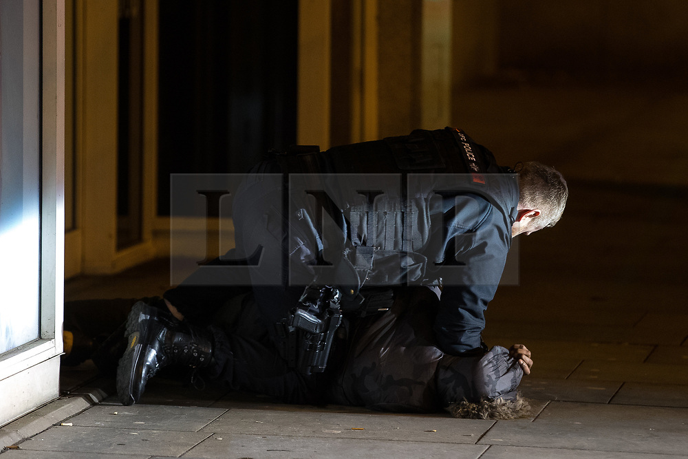 © Licensed to London News Pictures . 01/01/2018. Manchester, UK. Police detain and arrest a man on suspicion of robbery on Cross Street . Revellers celebrate the start of the New Year in Manchester City Centre . Photo credit: Joel Goodman/LNP