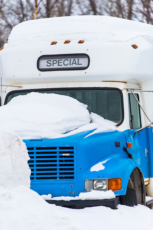 A bus with the word special parked in a snowbank in Michigan.