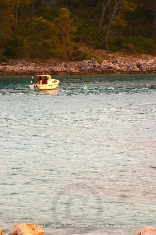 A boat moored at a buoy in the bay at Brna off the Korcula island at sunset. Prizba village. Korcula Island. Prizba, Riva Apartments, Danny Franulovic. Korcula Island. Dalmatian Coast, Croatia, Europe.