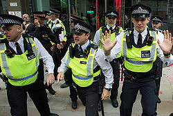 Metropolitan Police officers prepare to push back Extinction Rebellion activists after blood-red paint was spread across the facade of Standard Chartered bank during a Blood Money March through the City of London on 27th August 2021 in London, United Kingdom. Extinction Rebellion were intending to highlight the £23bn which they say Standard Chartered has invested in fossil fuels since the Paris Agreement whilst calling on the UK government to cease all new fossil fuel investment with immediate effect.