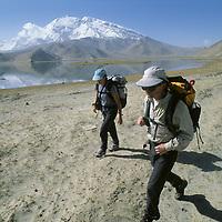CHINA, XINJIANG. Jeremy Schmidt & Nancy Feaghin (MR) trek by Lake Karakul in Pamir Mountains. 7546m Mustagh Ata background.