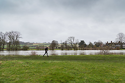 A runner makes his way along the towpath with the waters of the River Thames just inches from inundating the adjacent meadows. Heavy rains in the catchment area and saturated ground cause the river to rise to within inches of bursting its banks.. April 02 2018.
