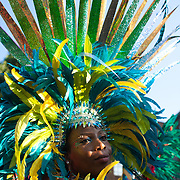 The setting sun hits a dancer wearing a headgear full of blue,green and yellow feathers and spikes. The Notting Hill Carnival has been running since 1966 and is every year attended by up to a million people. The carnival is a mix of amazing dance parades and street parties with a distinct Caribbean feel.